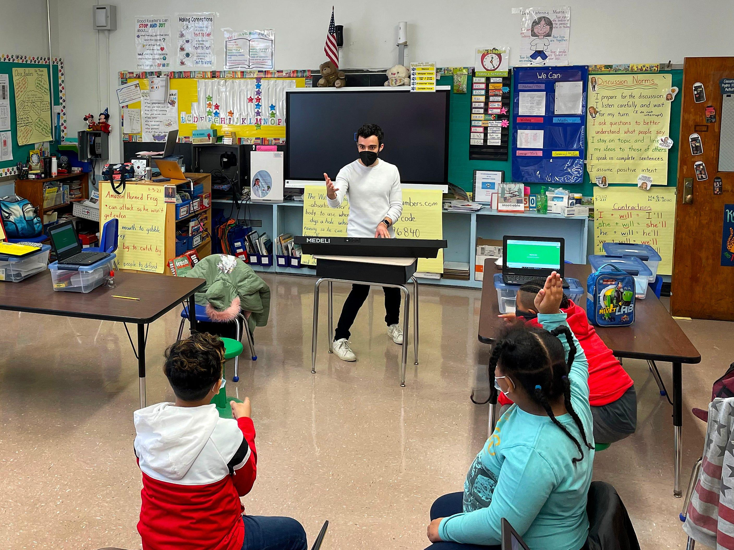Music teacher Andrew Grossman instructs students in a New York City classroom. Budget cuts because of the pandemic have meant that fewer students have the opportunity for instruction in music and the arts.
