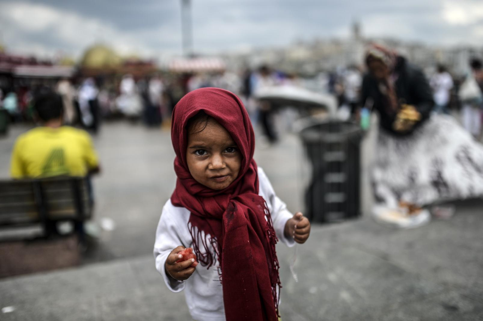 A Syrian refugee child eats food collected from a rubbish bin by her mother (background right), in Istanbul, Turkey, on August 18, 2014 (AFP Photo/Bulent Kilic)