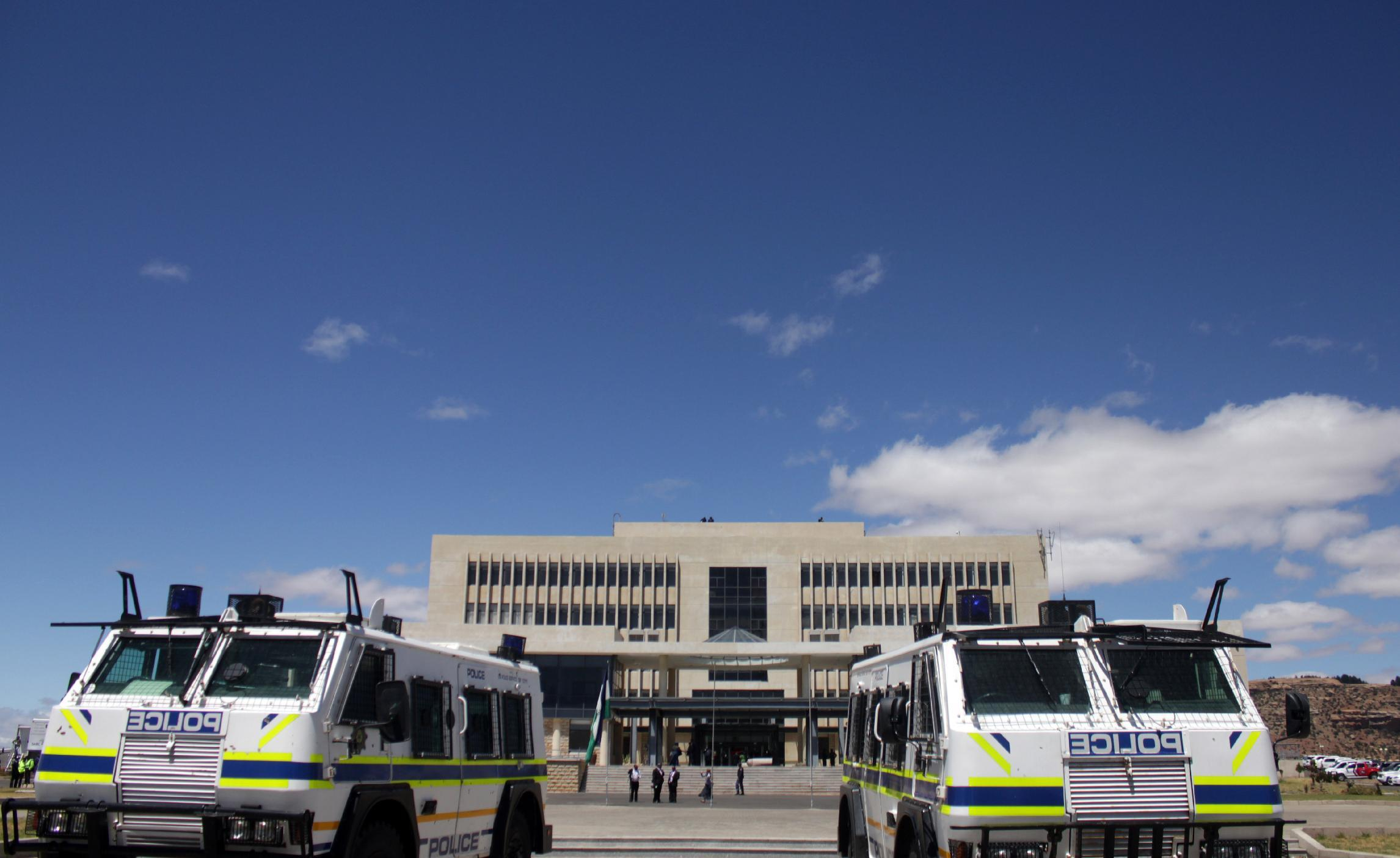 African Police trucks sit in front of the parliament building in Lesotho's capital Maseru on October 17, 2014 (AFP Photo/Hlompho Letsielo)