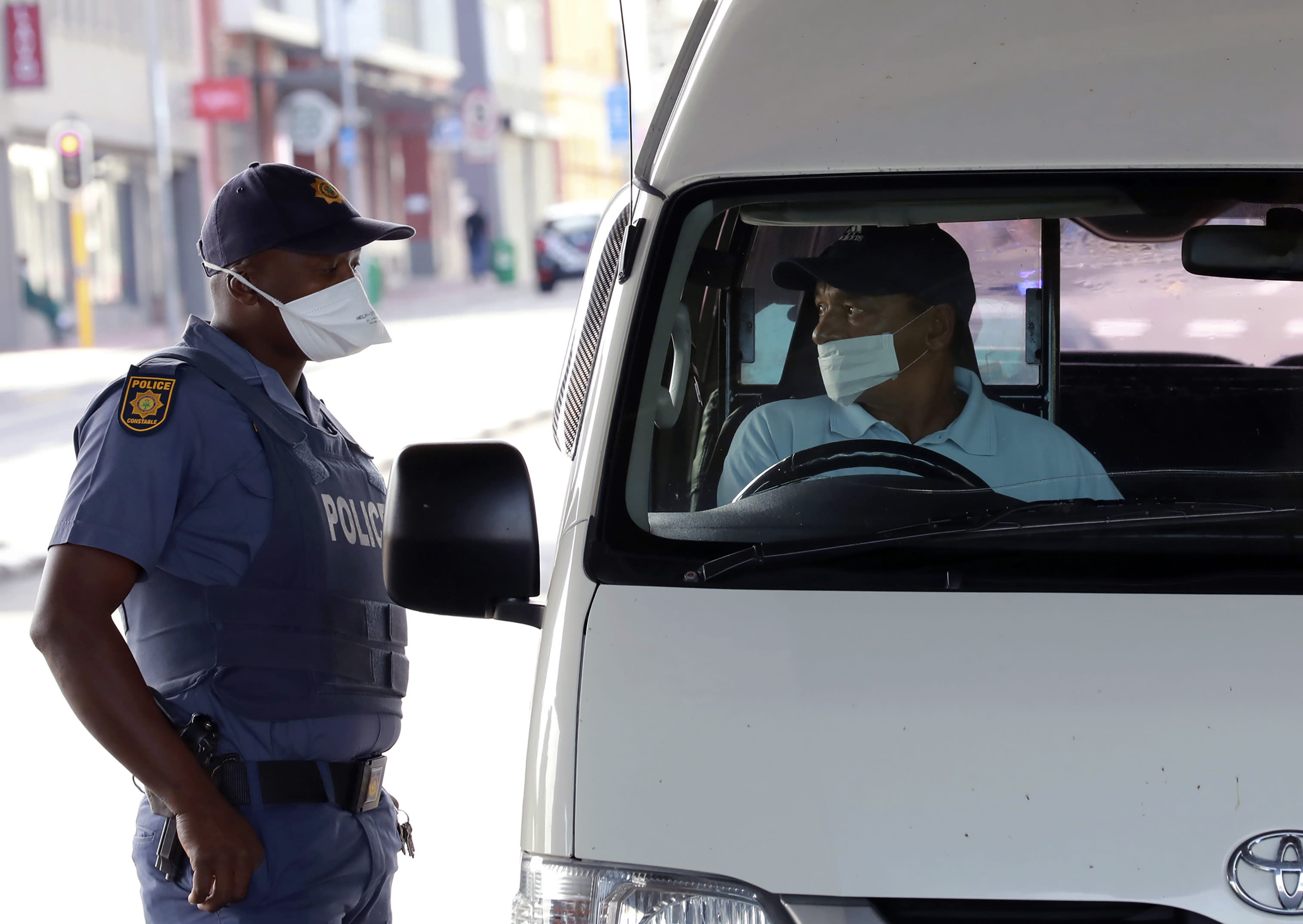 A policeman check the credentials of a motorist in Cape Town, South Africa, Friday, March 27, 2020, after South Africa went into a nationwide lockdown for 21 days in an effort to mitigate the spread to the coronavirus. The new coronavirus causes mild or moderate symptoms for most people, but for some, especially older adults and people with existing health problems, it can cause more severe illness or death(AP Photo/Nardus Engelbrecht)