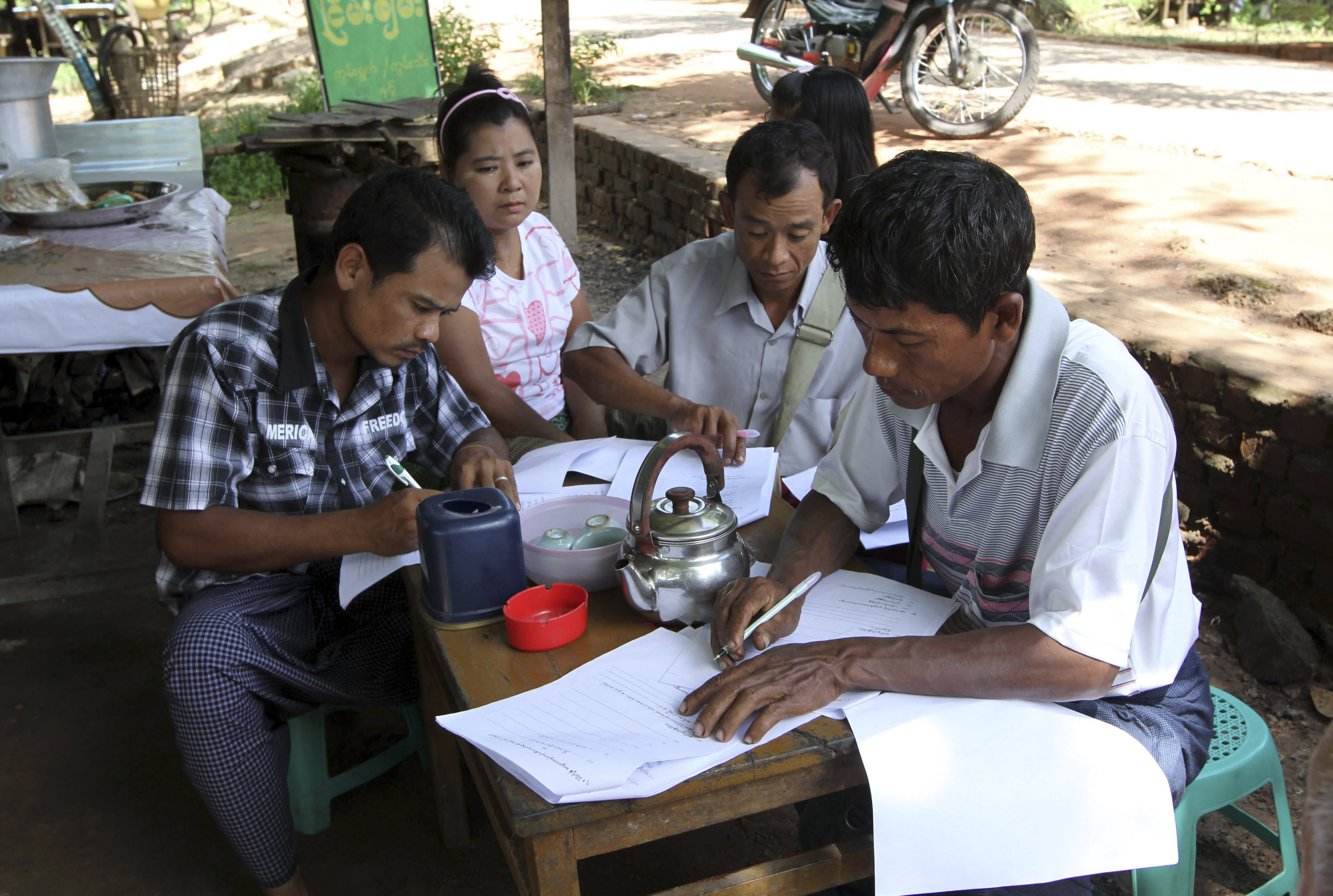In this photo taken on Sept. 15, 2012, Myanmar landless farmers gather outside the home of Nay Myo Wai, an activist and politician who is leading the farmers in their fight against the Zaykabar Company to sign and thumbprint petitions asking the company for more money, in Yangon, Myanmar. The landscape of Mingaladon township, northern outskirts of Yangon, tells a story of economic upheaval. Skeletons of factories for a new industrial zone rise from thick green rice paddies local farmers say were seized illegally by the Zaykabar Company, one of Myanmar's most powerful companies. Human rights groups say land battles could intensify because companies tied to the military and business elite are rushing to grab land as the country emerges from five decades of isolation and opens its economy. (AP Photo/Khin Maung Win)