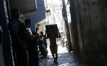 Police Peacekeeping Unit officers patrol an alley in Pavao-Pavaozinho slum in Rio de Janeiro