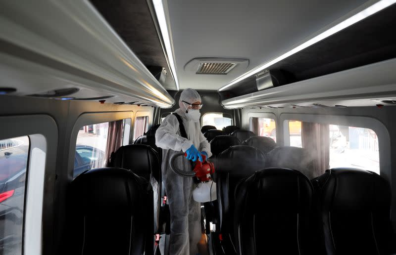 A Palestinian worker in a protective suit disinfects a bus as a preventive measure against the coronavirus in Beit Jala town in the Israeli-occupied West Bank