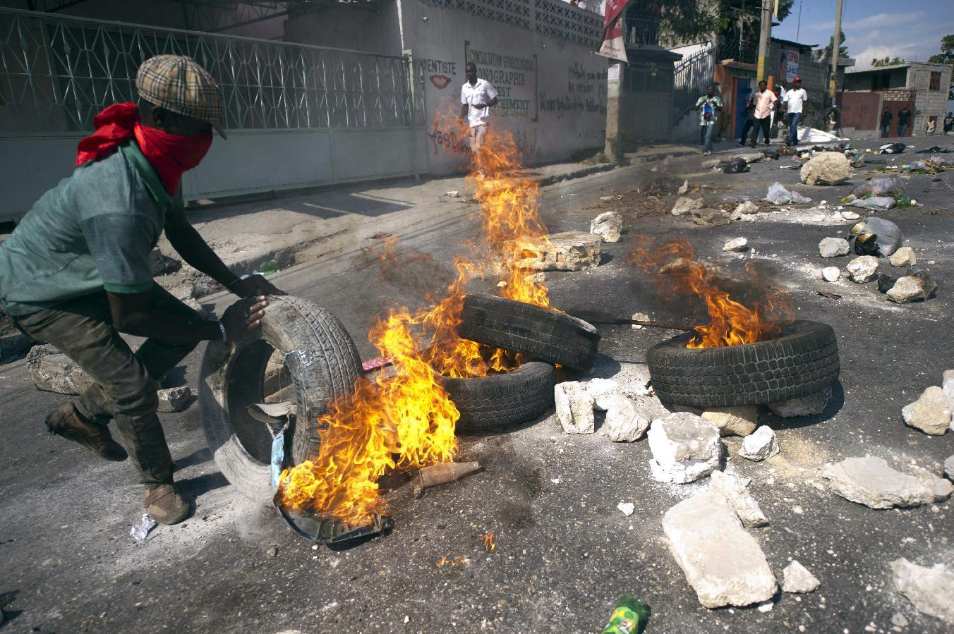 Protesters calling for the resignation of President Michel Martelly and Prime Minister Laurent Lamothe block a street with burning tires and barricades in the center of Port-au-Prince, on December 13, 2014 (AFP Photo/Hector Retamal)