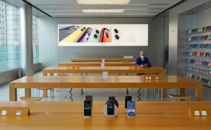 A man wearing face mask sits at an Apple Store in Hong Kong Wednesday, April 1, 2020.