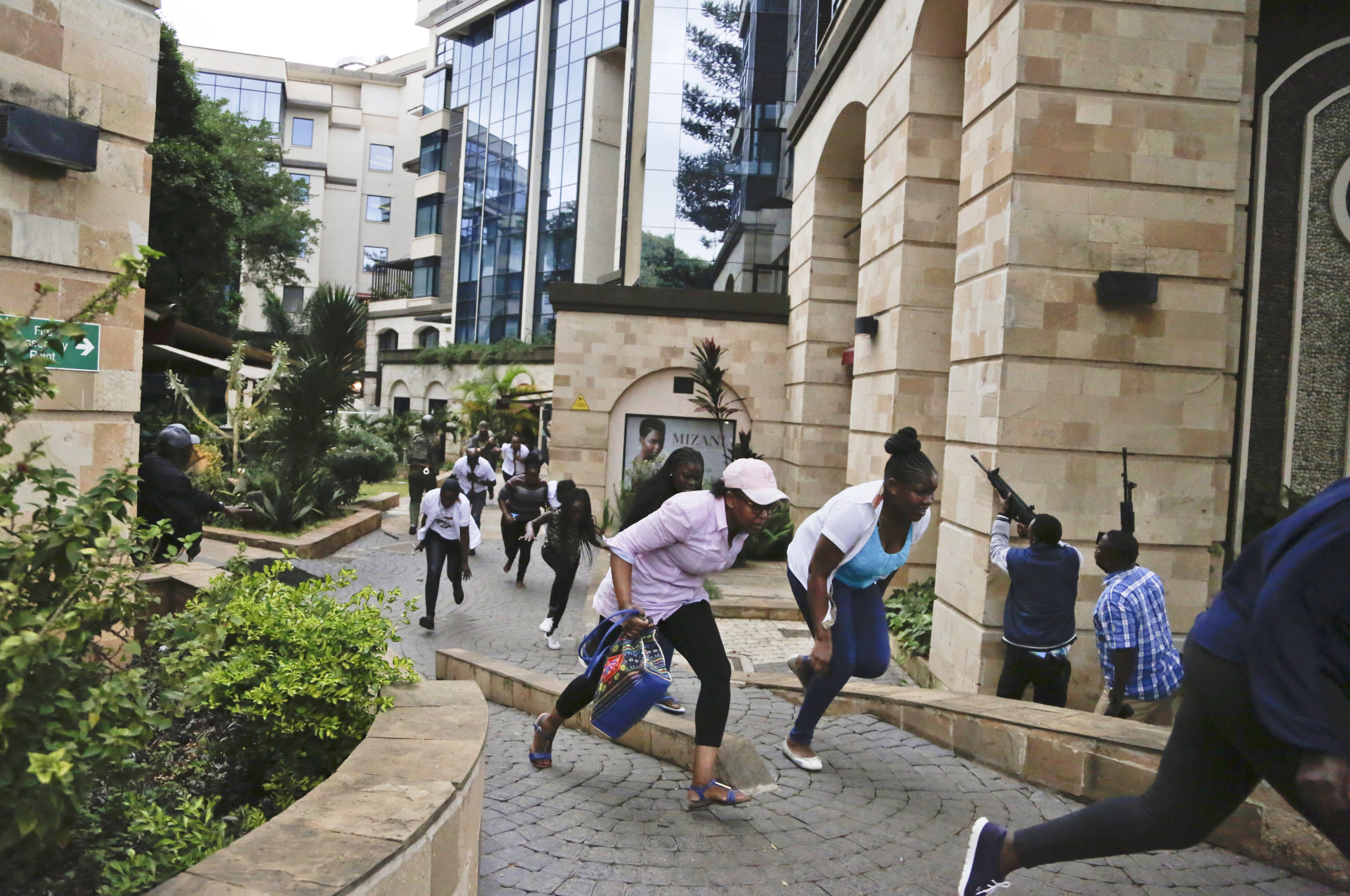 FILE - In this Jan. 15, 2019 file photo, people flee as security forces aim their weapons during a deadly attack by extremists at a luxury hotel complex in Nairobi, Kenya. Islamic extremists are already exploiting possible U.S. military cuts in Africa that have caused a rare bipartisan outcry in Washington, with lawmakers stressing the need to counter China and Russia and rein in a growing threat from fighters linked to the Islamic State group. (AP Photo/Khalil Senosi, File)
