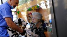 Spanish nursing home residents greet friends, family from behind windows