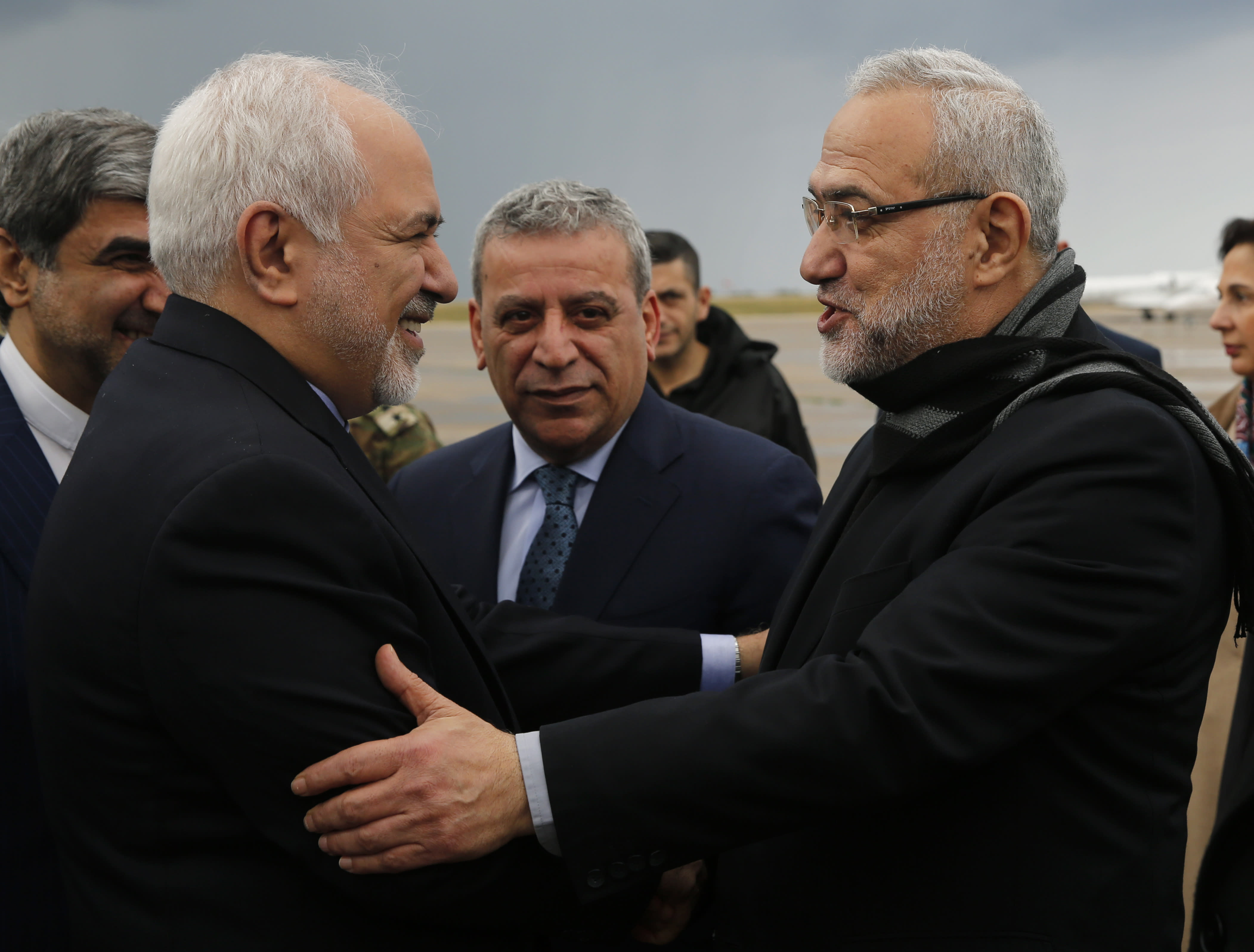 Iran's Foreign Minister Mohammad Javad Zarif, left, is greeted by Lebanese Minister of State Parliamentary Affairs and a member of Hezbollah politicians block Mahmoud Qmati, right, on his arrival at Rafik Hariri Airport, in Beirut, Lebanon, Sunday, Feb. 10, 2019. Zarif says his country is ready to cooperate with the new Lebanese government, offering his country's support in all sectors. (AP Photo/Hussein Malla)