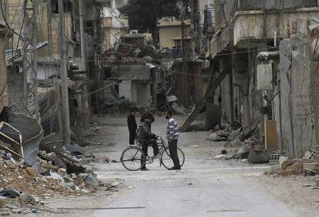 Men chat near buildings damaged by what activists said was shelling by forces loyal to Syria's President Bashar al-Assad in Daraya, near Damascus
