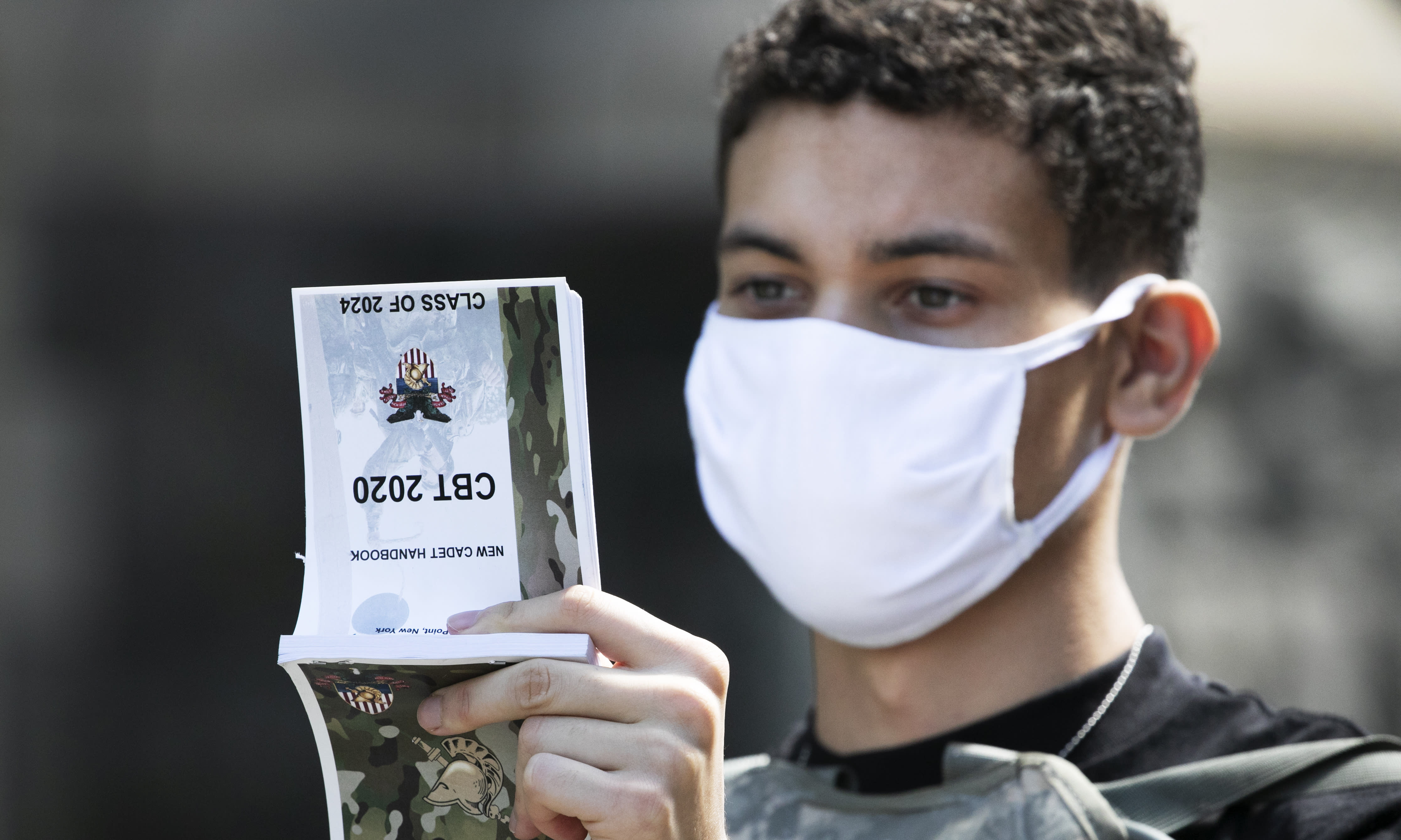 A West Point cadet reads the New Cadet Handbook on his first day at the U.S. Military Academy, Monday, July 13, 2020, in West Point, N.Y. The Army is welcoming more than 1,200 candidates from every state. Candidates will be COVID-19 tested immediately upon arrival, wear masks, and practice social distancing. (AP Photo/Mark Lennihan)