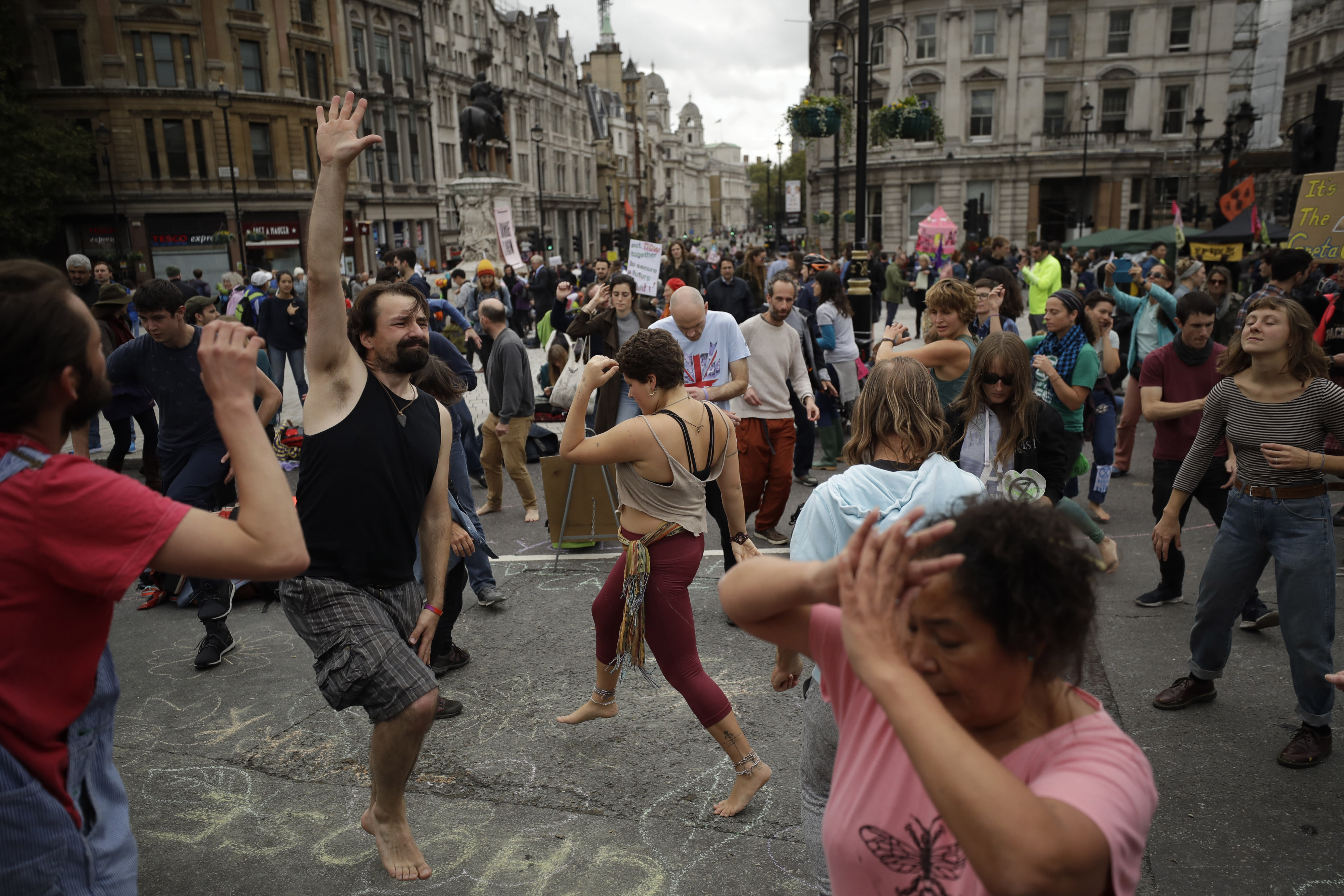 Extinction Rebellion climate change protesters dance to music as they block a street at the bottom of Trafalgar Square in London, Tuesday, Oct. 8, 2019. Hundreds of climate change activists camped out in central London on Tuesday during a second day of world protests by the Extinction Rebellion movement to demand more urgent actions to counter global warming. (AP Photo/Matt Dunham)