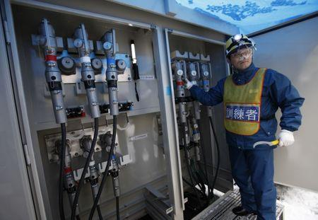 An employee of Kansai Electric Power Co's stands during a demonstration before an inspection by the IAEA members at Ohi nuclear power plant in Ohi