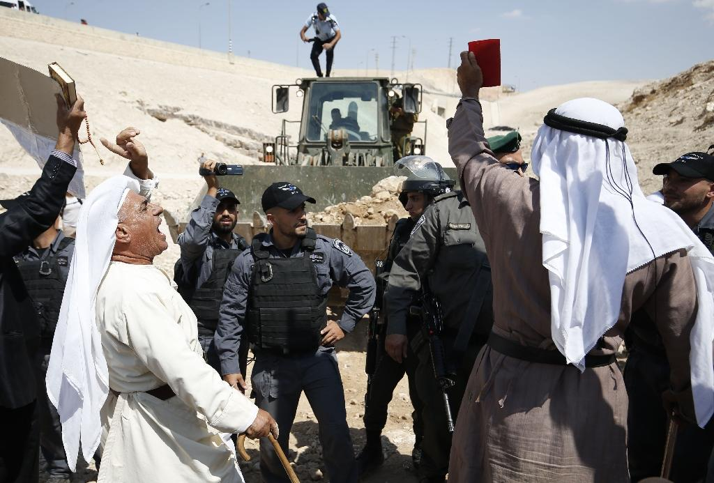 Palestinian protestors confront Israeli forces as an Israeli bulldozer seeks to close off a route to the Bedouin village of Khan al-Ahmar by dumping rocks and earth on it