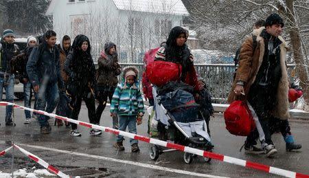 Migrants stay in queue before passing Austrian-German border
