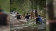 Hikers in Arizona floodwaters form human chain to help pull each other to safety