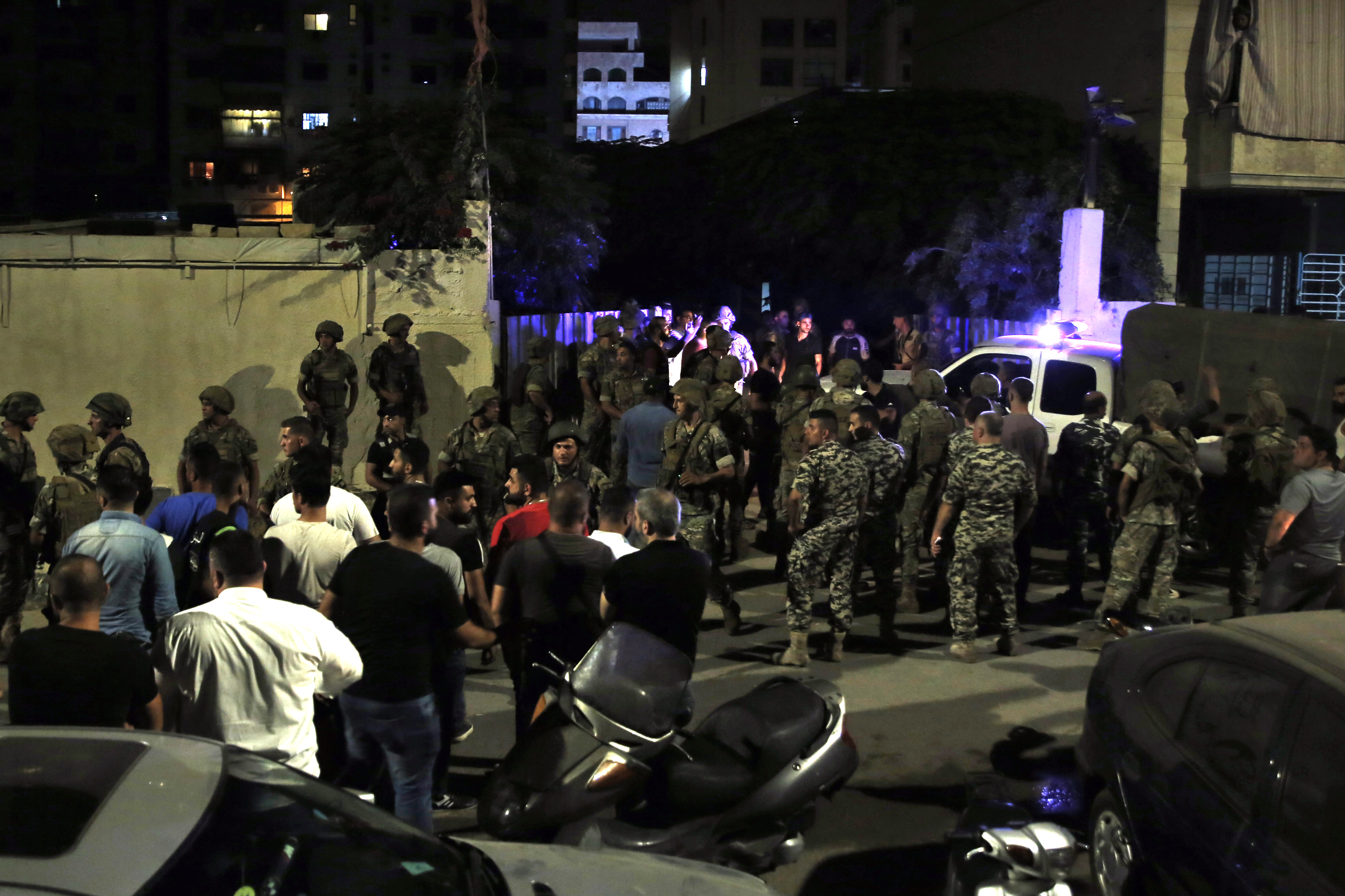 Lebanese security stand at the site where an Israeli drone was said to have crashed in a stronghold of the Lebanese Hezbollah group, in a southern suburb of Beirut, Lebanon, Sunday, Aug. 25, 2019. A Hezbollah official said Sunday that an Israeli drone went down over the Lebanese capital of Beirut and another exploded in the air, amid regional tensions between Israel and Iran. (AP Photo/Bilal Hussein)