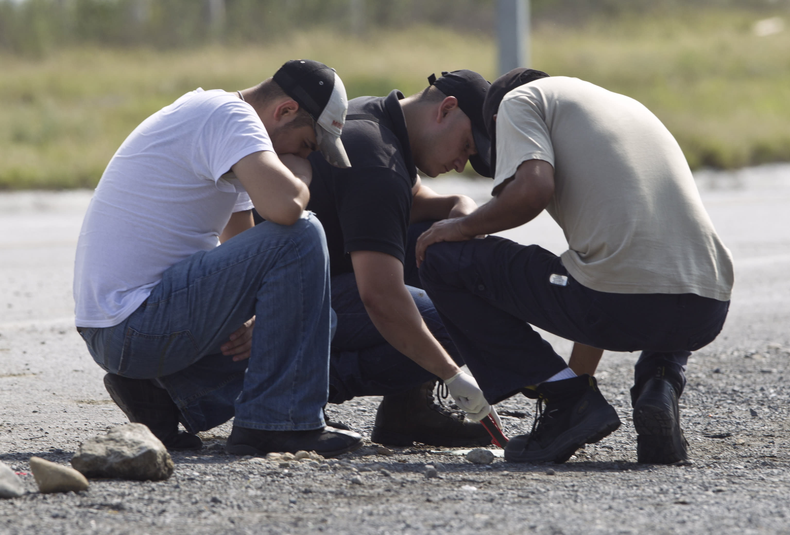 FILE - In this May 13, 2012 file photo, forensic experts examine the area where dozens of bodies, some of them mutilated, were found on a highway connecting the northern Mexican metropolis of Monterrey, Mexico, to the U.S. border. Two months after police found 49 dismembered bodies strewn on a Mexican highway leading to the Texas border, authorities have not identified a single victim. (AP Photo/Christian Palma, File)