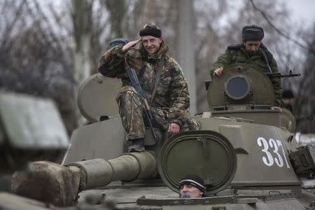 An armed man with the separatist self-proclaimed Donetsk People's Republic army salutes from the top of a mobile artillery cannon as his convoy starts pulling back from Donetsk February 28, 2015. REUTERS/Baz Ratner