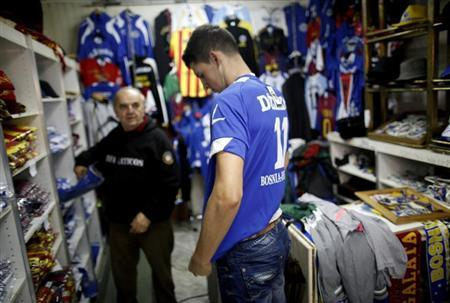 A tourist tries on a Bosnian national soccer team jersey at a shop in the old part of the city in Sarajevo