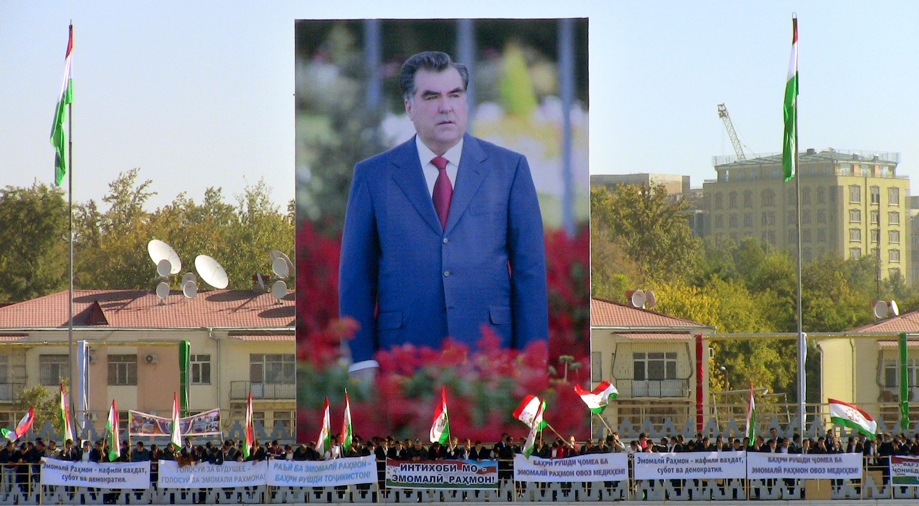People wave Tajik flags in front of a giant poster of Tajikistan's President Emomali Rakhmon during a rally in Dushanbe, on November 3, 2013 (AFP Photo/)