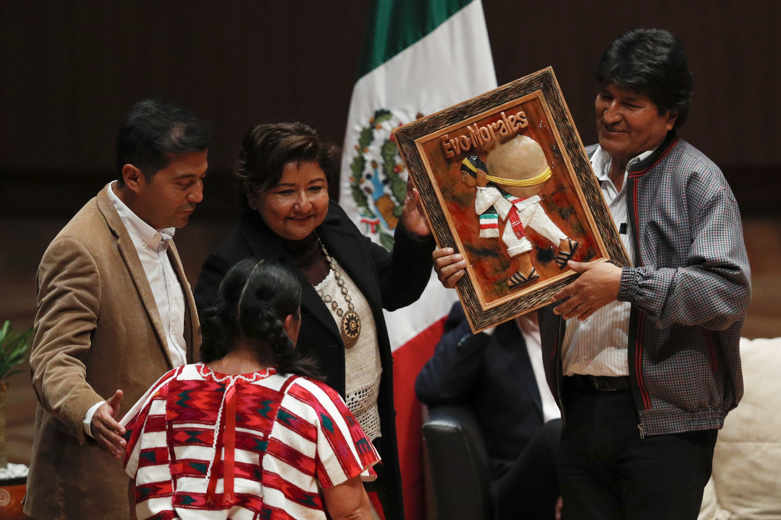 Members of an indigenous community present Bolivia's former President Evo Morales, right, with an artwork during a dialog with students and indigenous communities, at Ollin Yoliztli Cultural Center in Mexico City, Tuesday, Nov. 26, 2019. Bolivia is struggling to stabilize after weeks of anti-government protests and violence in which at least 30 people have been killed. Former president Evo Morales resigned on Nov. 10 after an election that the opposition said was rigged. (AP Photo/Rebecca Blackwell)