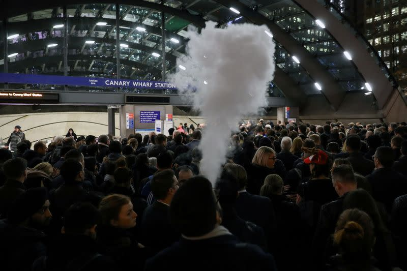 FILE PHOTO: A man smokes an e-cigarette in the queue to Canary Wharf tube station