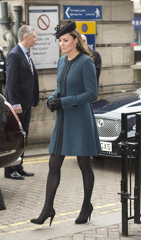 Kate visits the Baker Street Underground Station in this teal Malene Birger coat, and true to royal style: a pretty black fascinator.