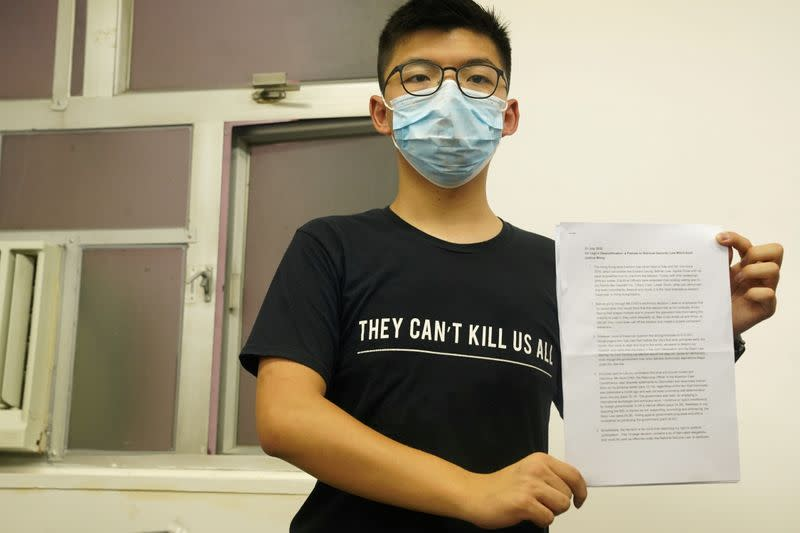 Hong Kong democracy activist Joshua Wong, wearing a face mask, shows journalists his declaration in English regarding his disqualification as a candidate in elections for the legislature, during a news conference in Hong Kong