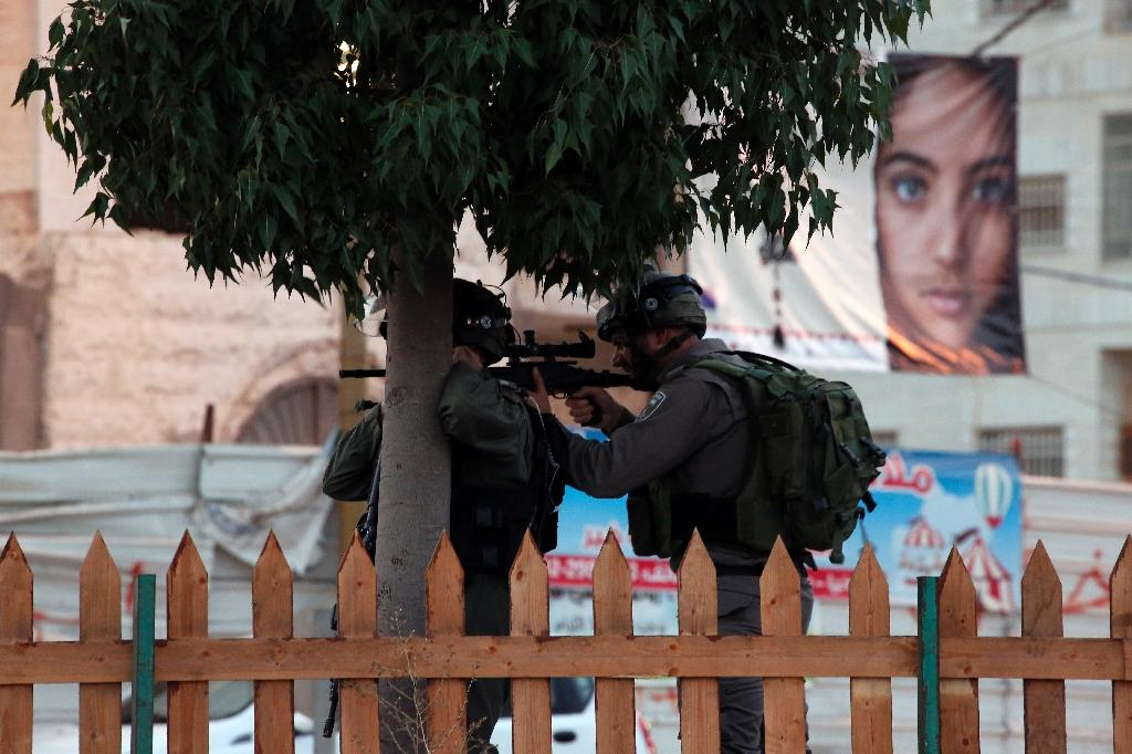Israeli soldiers take aim during clashes with Palestinian youth close to the Jewish settlement of Bet El, in the West Bank city of Ramallah on October 4, 2015