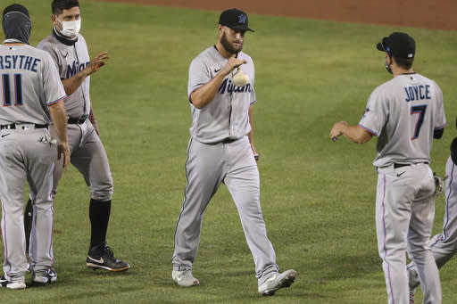 Miami Marlins pitcher Josh A. Smith celebrates his win with teammates following the tenth inning of a baseball game against the Toronto Blue Jays, Wednesday, Aug. 12, 2020, in Buffalo, N.Y. (AP Photo/Jeffrey T. Barnes)