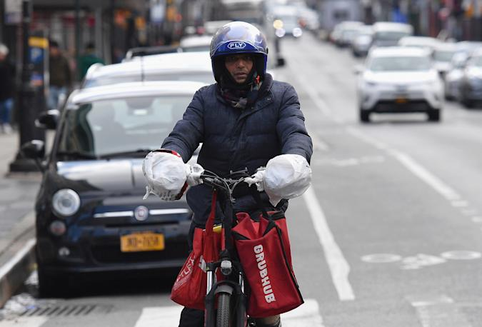 A delivery person rides his bike in Brooklyn, New York on March 17, 2020. - Food delivery workers have become essential in New York after the city closed restaurants and bars to the public on March 16th, 2020. They are taking extreme precautions not to get sick, but most of them are immigrants with no papers and no health insurance. (Photo by Angela Weiss / AFP) (Photo by ANGELA WEISS/AFP via Getty Images)
