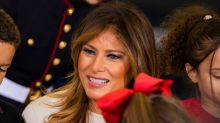Melania Trump Wears Candy Cane Stripes With Red Slouch Boots at Toys for Tots Event