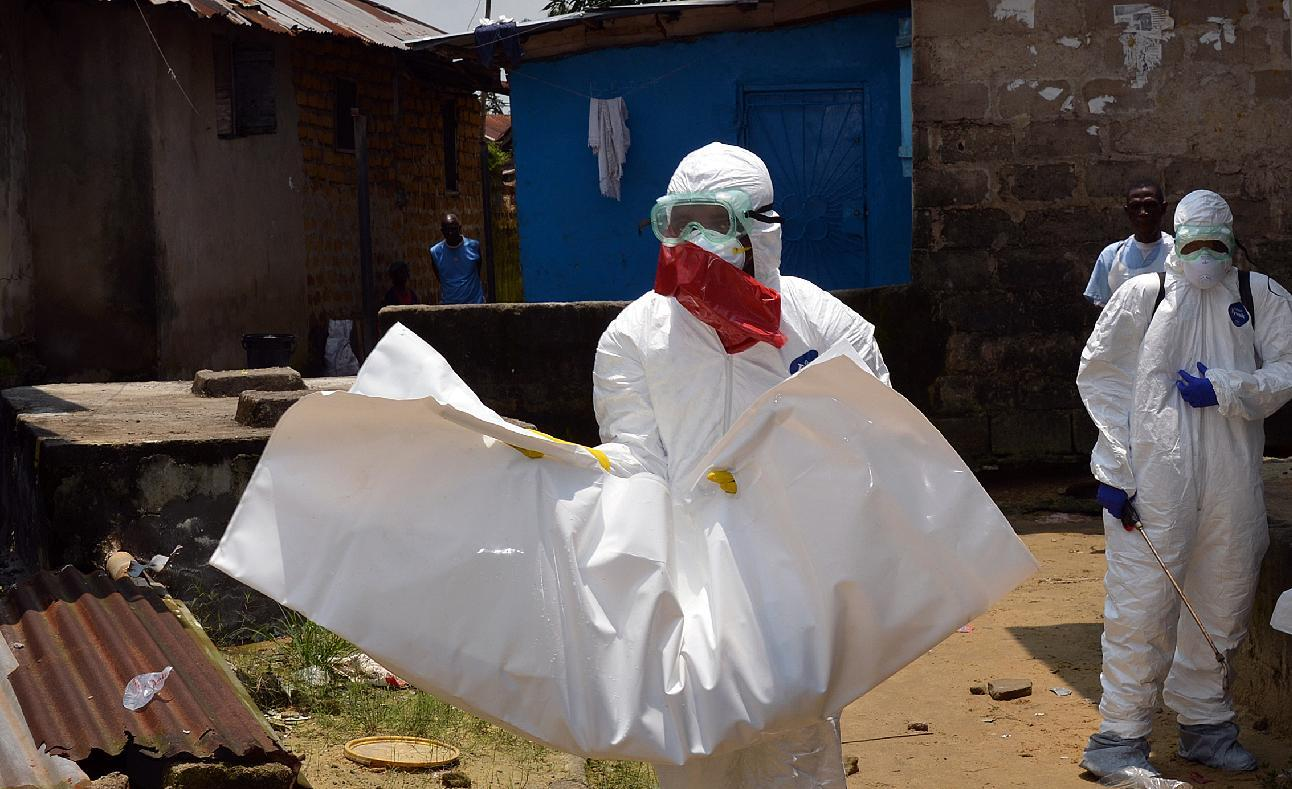 Liberian Red Cross health workers, wearing protective suits, carry the body of a 18-old-month baby, victim of the Ebola virus on September 12, 2014