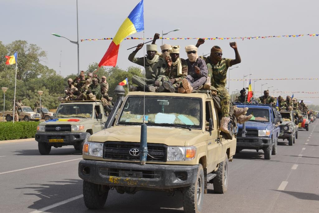 Chadian soldiers wave to the crowd in the capital N'djamena during a homecoming from neighbouring Niger where they were fighting Boko Haram (AFP Photo/Brahim Adji)