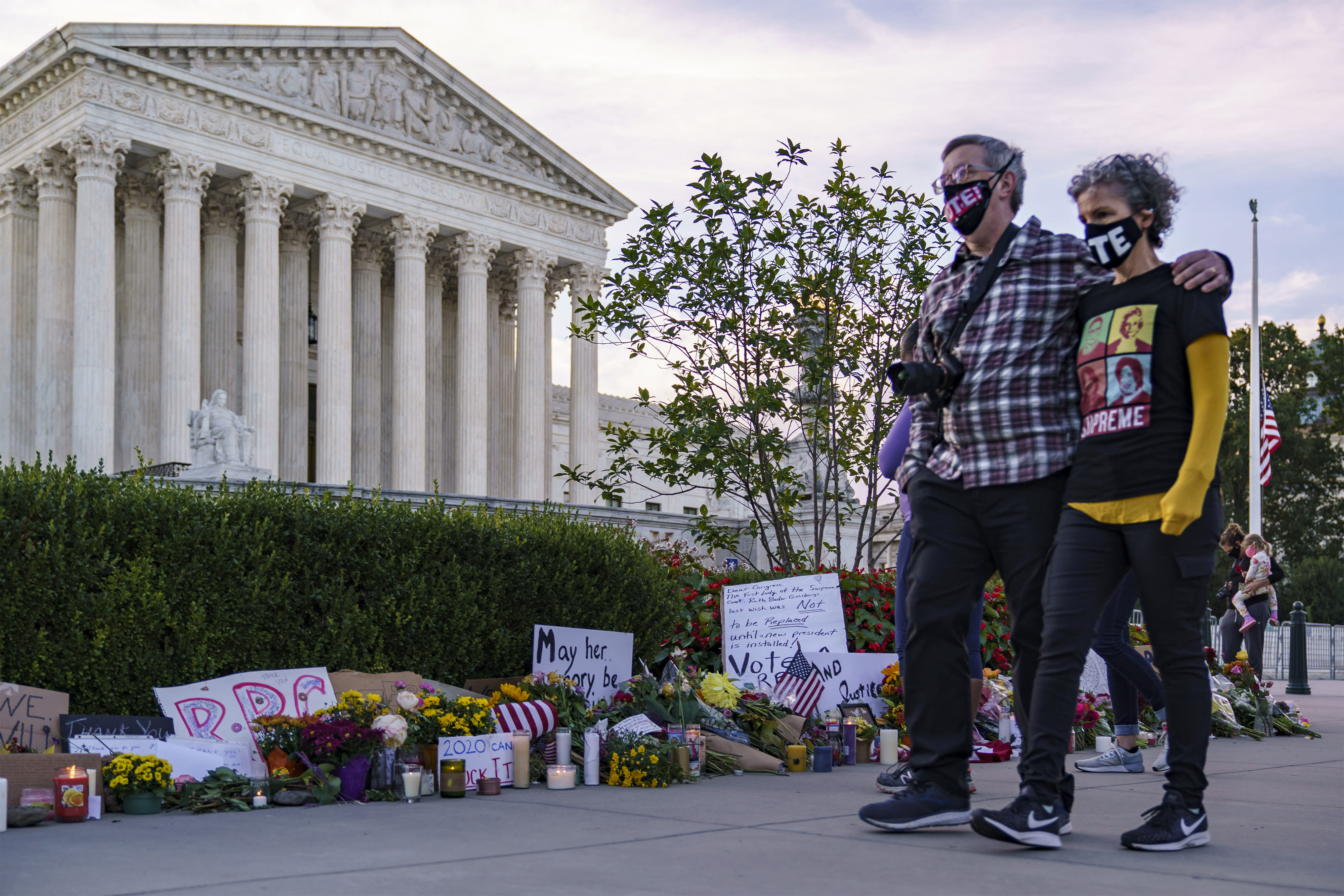 People gather at the Supreme Court on the morning after the death of Justice Ruth Bader Ginsburg, 87, one of the high court's liberal justices, and a champion of gender equality, in Washington, Saturday, Sept. 19, 2020. (AP Photo/J. Scott Applewhite)