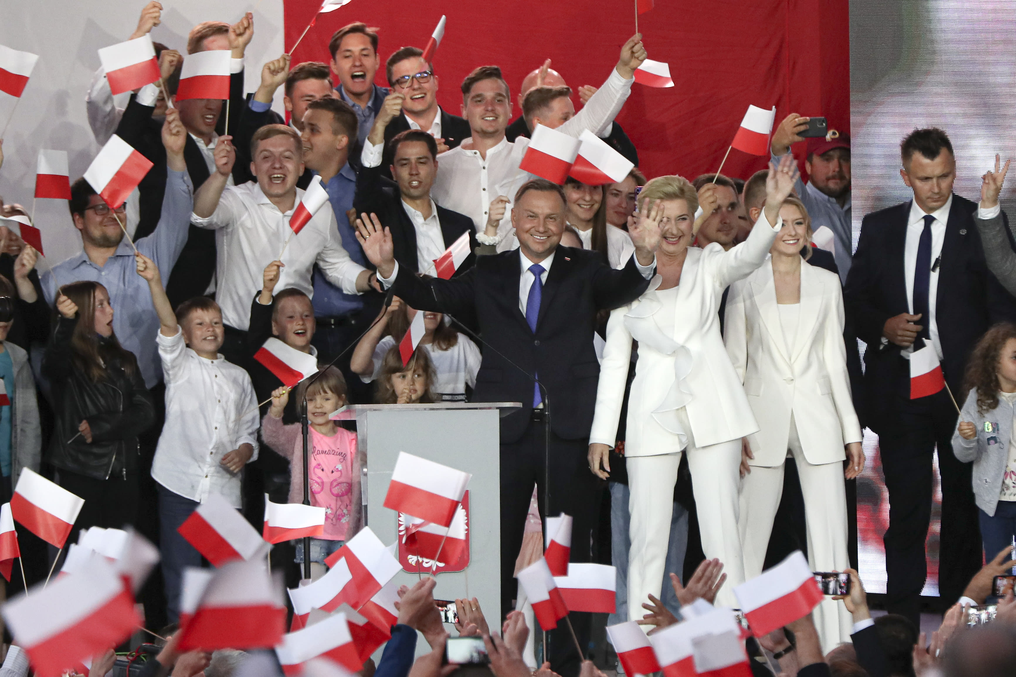 Incumbent President Andrzej Duda, left, and his wife Agata Kornhauser-Duda wave to supporters in Pultusk, Poland, Sunday, July 12, 2020. Conservative Duda ran against liberal Warsaw Mayor Rafal Trzaskowski in a razor-blade-close presidential election runoff and exit poll shows election is too close to call. (AP Photo/Czarek Sokolowski)