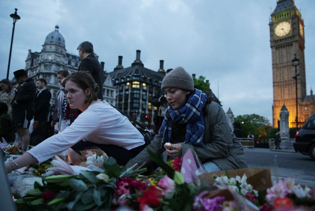 People place floral tributes and candles to slain Labour MP Jo Cox at a vigil in Parliament square in London on June 16, 2016 (AFP Photo/Daniel Leal-Olivas)