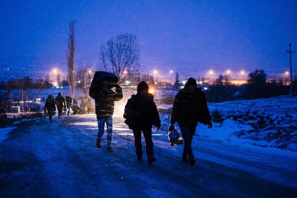 Migrants and refugees walk on a snow covered street after crossing the Macedonian border into Serbia near the village of Miratovac on January 17, 2016 (AFP Photo/Dimitar Dilkoff)