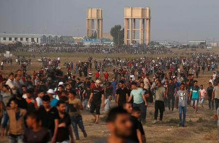 Palestinian demonstrators gather at the Israel-Gaza border fence during a protest calling for lifting the Israeli blockade on Gaza and demanding the right to return to their homeland, in Gaza October 19, 2018. REUTERS/Mohammed Salem