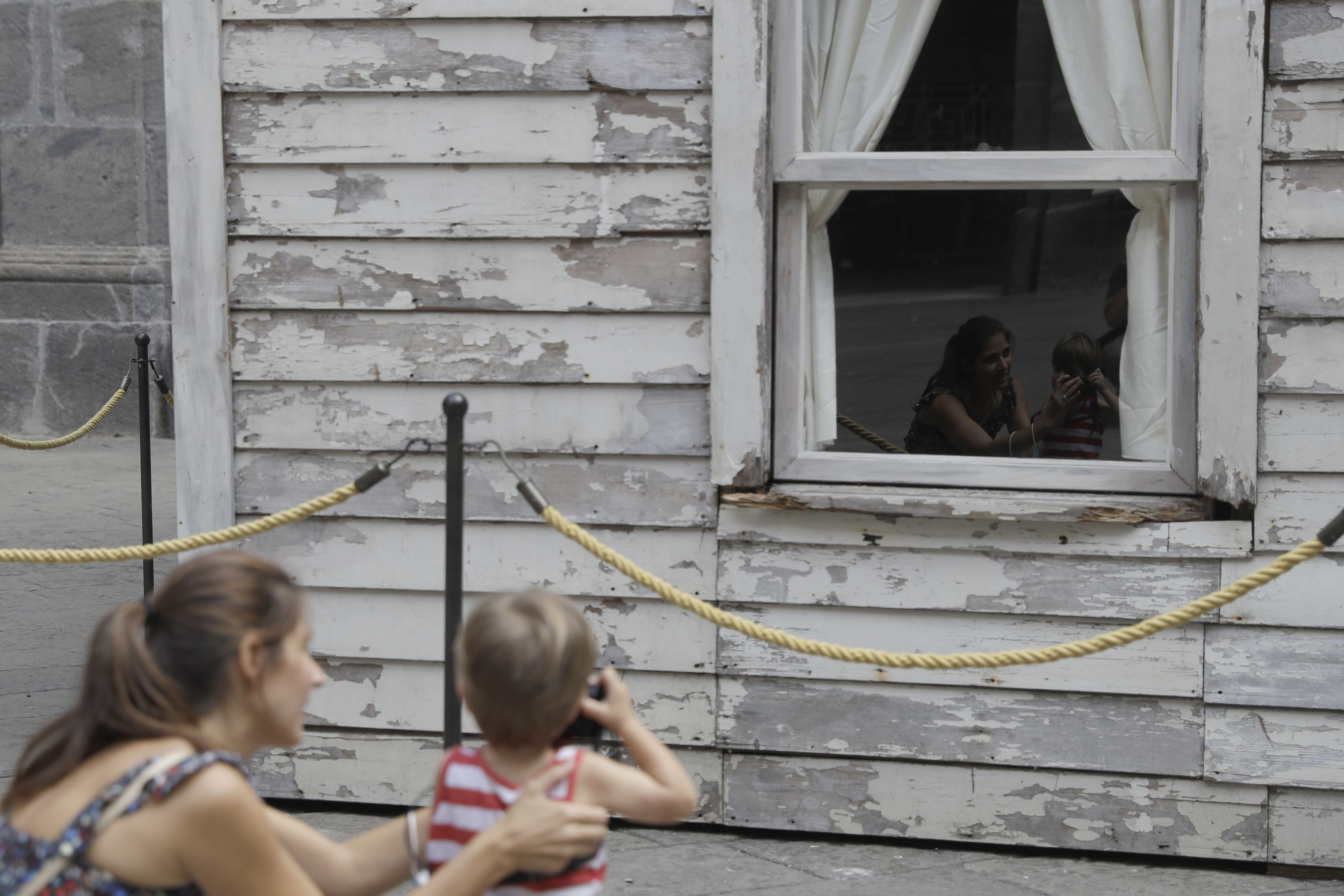 Alice Ridolfi, from Verona, helps her two-year-old son Leone take pictures of the house of U.S. civil rights campaigner Rosa Parks, rebuilt by artist Ryan Mendoza for public display in Naples, Italy, Tuesday, Sept. 15, 2020. The rundown, paint-chipped Detroit house where Parks took refuge after her famous bus boycott is going on display in a setting that couldn't be more incongruous: the imposing central courtyard of the 18th century Royal Palace. (AP Photo/Gregorio Borgia)