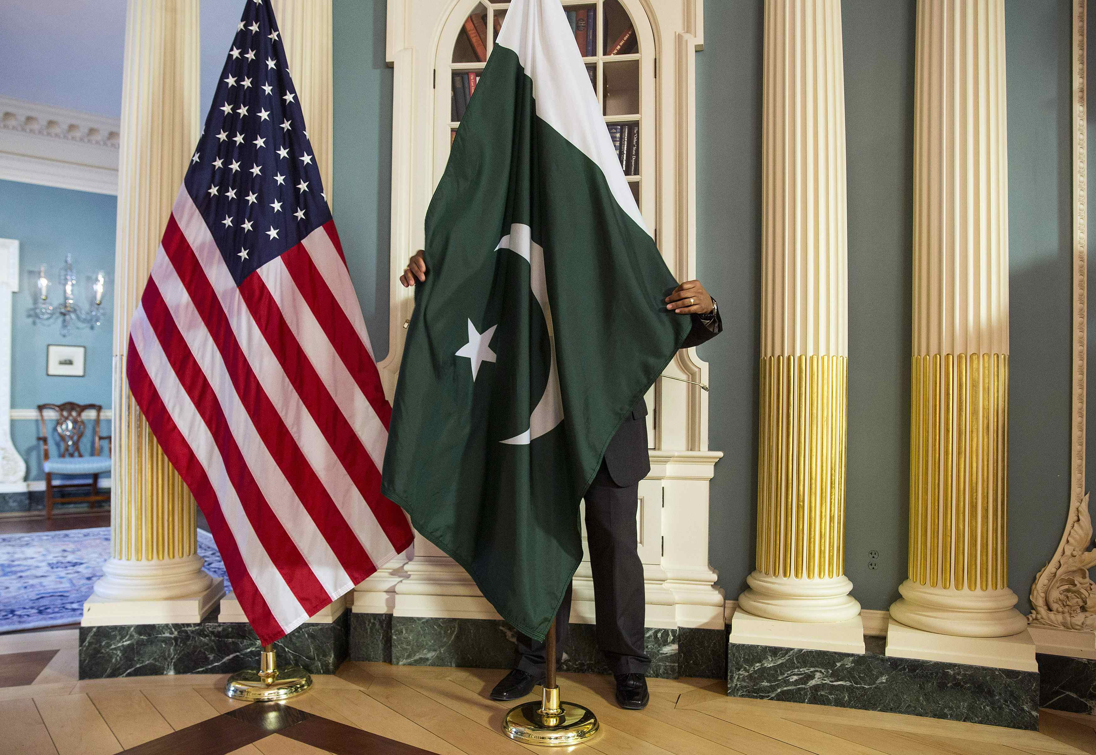 A State Department contractor adjust a Pakistan national flag before a meeting between U.S. Secretary of State John Kerry and Pakistan's Interior Minister Chaudhry Nisar Ali Khan on the sidelines of the White House Summit on Countering Violent Extremism at the State Department in Washington February 19, 2015. REUTERS/Joshua Roberts (UNITED STATES - Tags: POLITICS)