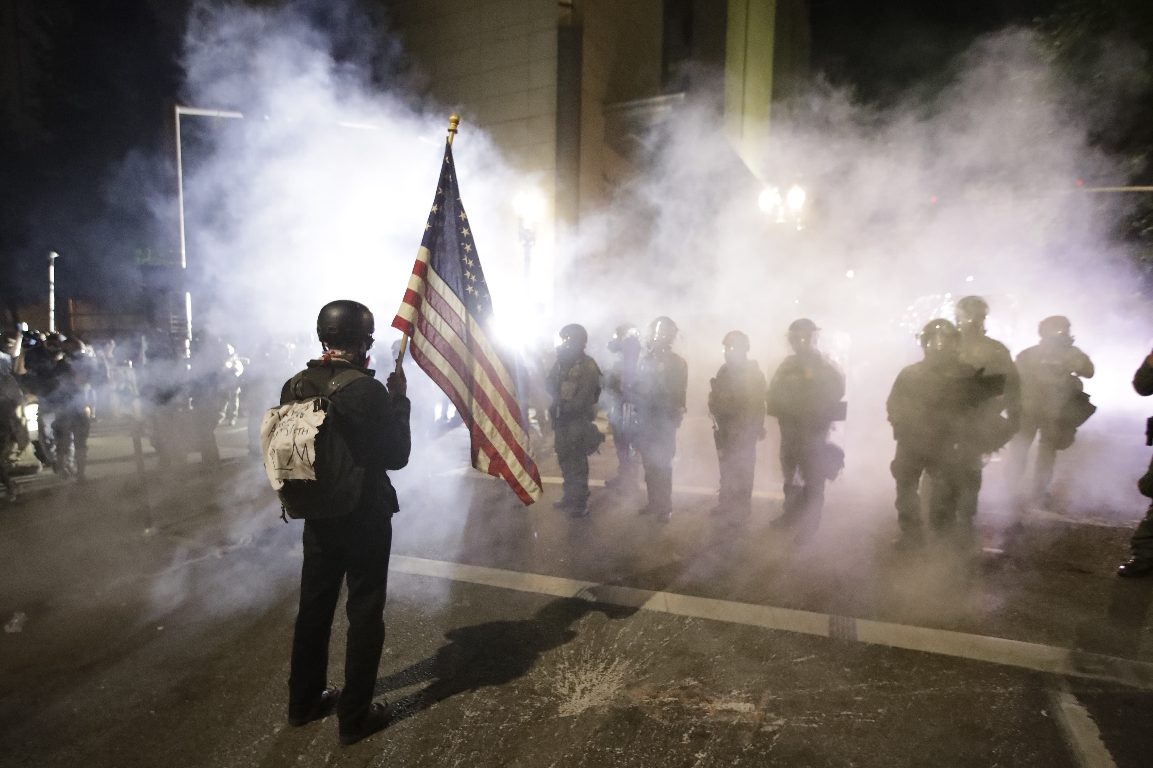 A demonstrator waves a U.S. flags in front of federal agents after tear gas is deployed during a Black Lives Matter protest at the Mark O. Hatfield United States Courthouse Thursday, July 30, 2020, in Portland, Ore. (AP Photo/Marcio Jose Sanchez)