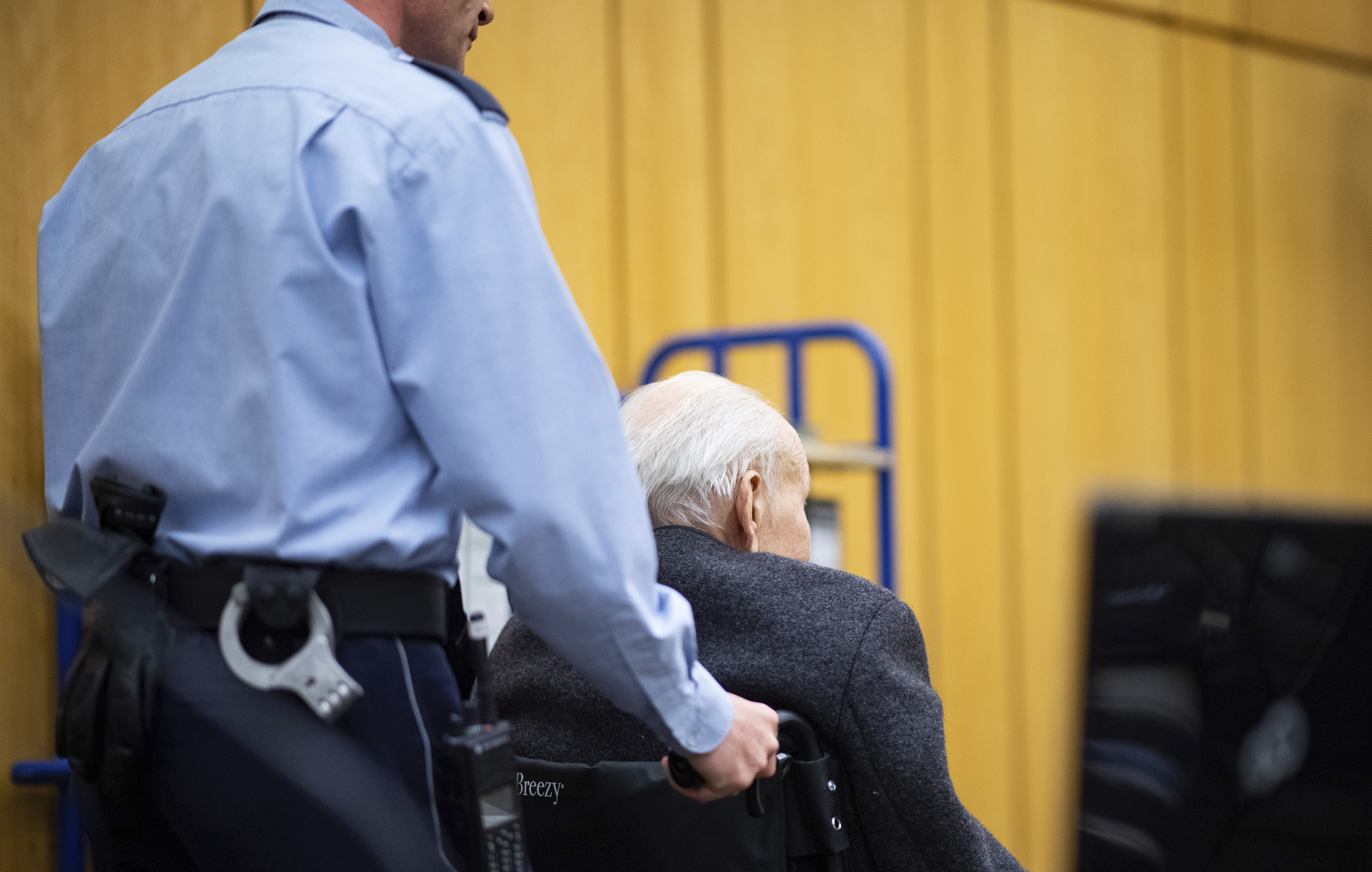 Johann Rehbogen, a 94-year-old former SS enlisted man, who is accused of hundreds of counts of accessory to murder for alleged crimes committed during the years he served as a guard at the Nazis' Stutthof concentration camp, sits in a wheelchair when arriving for the beginning of the third day of his trial at the regional court in Muenster, western Germany, Tuesday, Nov. 13, 2018. (Guido Kirchner/pool photo via AP)