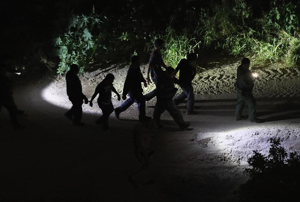 A US Border Patrol agent leads a group of captured undocumented immigrants near the US-Mexico border near Hidalgo, Texas (AFP Photo/JOHN MOORE)