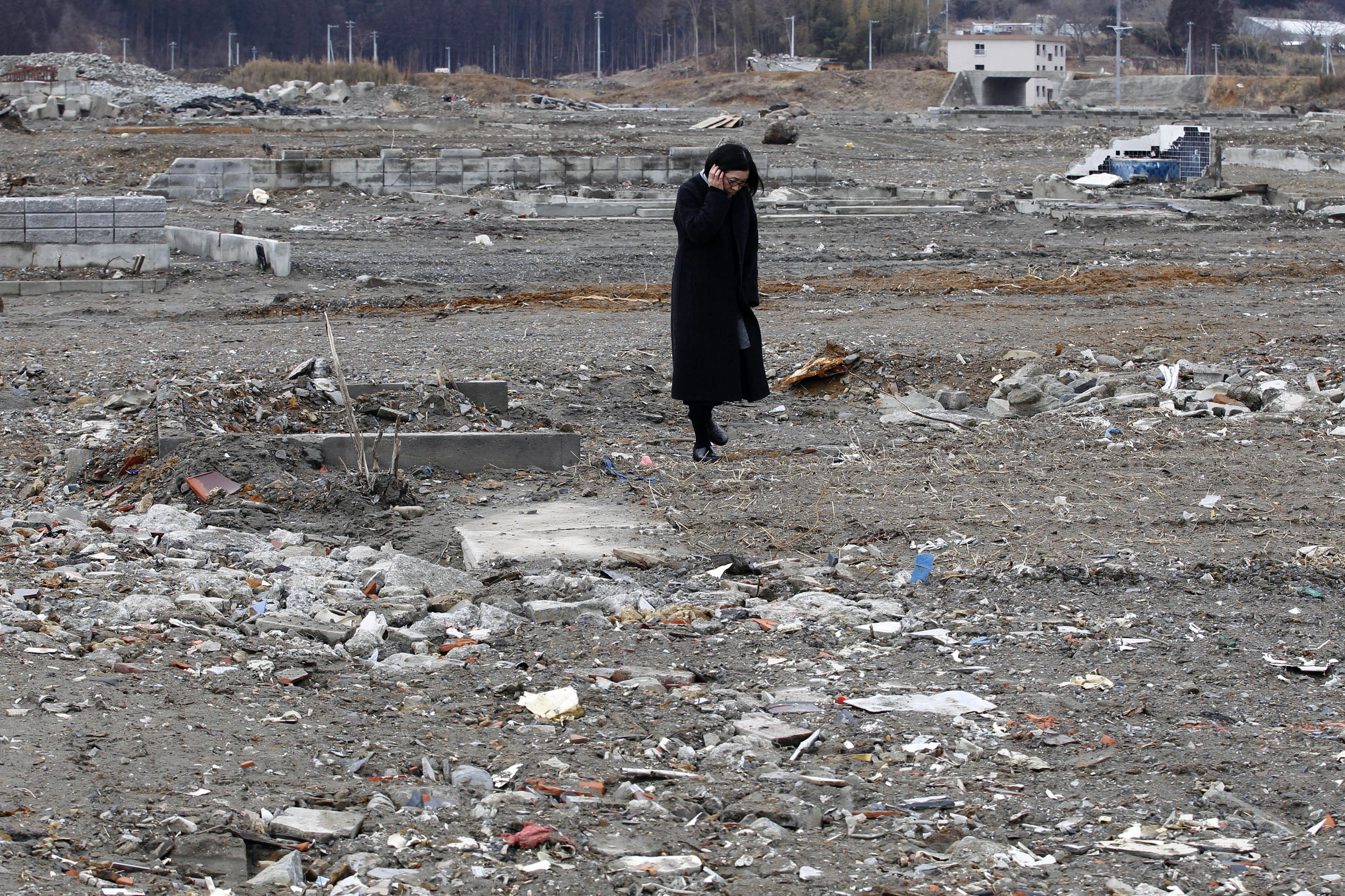 A woman stands in an area devastated by the March 11, 2011 earthquake and tsunami, in Minamisanriku, Miyagi Prefecture, Sunday, March 11, 2012. Japan on Sunday was remembering the massive earthquake and tsunami that struck the nation a year ago, killing just over 19,000 people and unleashing the world's worst nuclear crisis in a quarter century.(AP Photo/Shizuo Kambayashi)