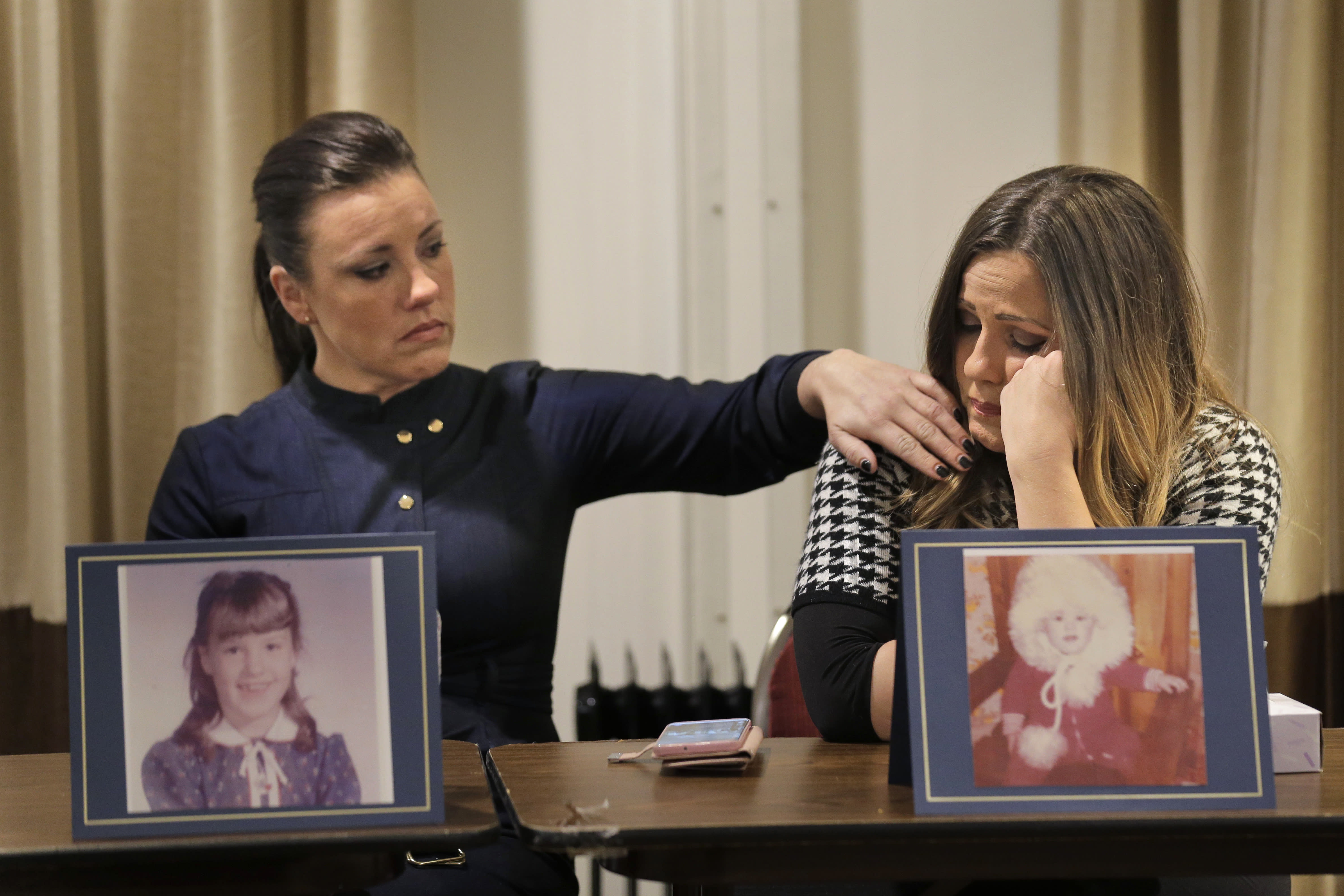 Teresa Forteny-Miller, left, comforts her sister Carolyn Fortney as they sit behind pictures of themselves as children as they listen to their other sisters speak during a news conference in Newark, N.J., Monday, Dec. 2, 2019. Two of the sisters from Pennsylvania are suing the Archdiocese of Newark and the Diocese of Harrisburg, Pennsylvania. They allege clergy in Newark knew a priest had sexually abused children before he moved to Harrisburg and abused them and their sisters for years. Lawsuits alleging sexual abuse by Roman Catholic clergy are taking center stage in New Jersey as the state's relaxation of statute of limitations rules takes effect. (AP Photo/Seth Wenig)