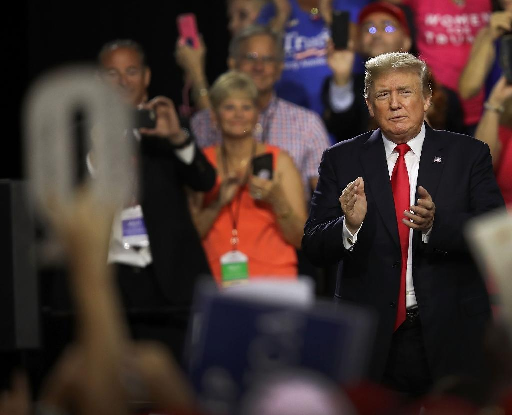 """Followers of QAnon believe President Donald Trump has given them hints, including pointing at people who wear """"Q"""" gear at his rallies, that validate their conspiracy theories (AFP Photo/JOE RAEDLE)"""