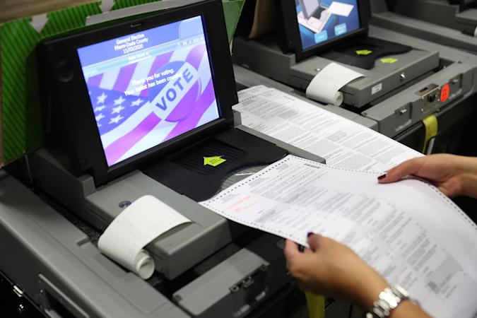 DORAL, FLORIDA - OCTOBER 14: A Miami-Dade election worker feeds ballots into a voting machines during an accuracy test at the Miami-Dade Election Department headquarters on October 14, 2020 in Doral, Florida. The test was done as the county prepares for the November 3rd election where President Donald Trump and Democratic presidential candidate Joe Biden are facing off against each other. (Photo by Joe Raedle/Getty Images)