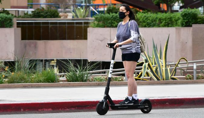 """A commuter on electric scooter wears her facemask  in Los Angeles on June 29, 2020 where the largest single-day number of new COVID-19 cases in the county since the pandemic began was confirmed, with a spike among the younger population. - The coronavirus pandemic is """"not even close to being over"""", the WHO warned today, as the global death toll passed half a million and cases surge in Latin America and the United States. (Photo by Frederic J. BROWN / AFP) (Photo by FREDERIC J. BROWN/AFP via Getty Images)"""