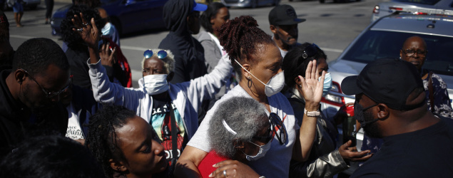 Odessa Riley, center in red, the mother of David McAtee, is embraced as she prays with family members on Monday near the site of his death in Louisville, Ky. McAtee, who owned a popular barbecue stand, was shot as the police and National Guard confronted curfew violators. (Luke Sharrett/New York Times)